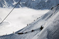 Snow slope with mountain skiers mont blanc against a white clouds and peaks of the alps france Stock Photos