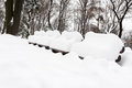 Snow winter in a park wooden benches full of Stock Photos
