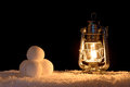 Snowballs and lantern illuminated by the light of an oil filled lamp Royalty Free Stock Image