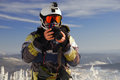 Snowboarder with camera action on helmet and slr in his hands Stock Photography