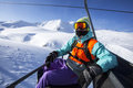 Snowboarder on the chairlift at chair lift going to summit Royalty Free Stock Photo
