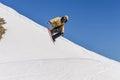 Snowboarder enjoying runs and jumps on spring`s last snow.