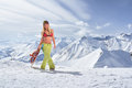 Snowboarder girl in a swimsuit walking on top of mountain Royalty Free Stock Photo