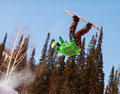 Snowboarder jumping through air with deep blue sky in background Stock Photo