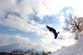 Snowboarder mid backflip at hanazono backcountry jump