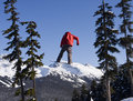 Snowboarder in red coat whistler canada january an anonymous with a bright jumping near blackcomb mountain he is framed by trees Stock Images