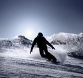 Snowboarder silhouette goes down by the high mountain ski slope Royalty Free Stock Photo