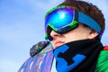 Snowboarder young man in sport sunglasses with a snowboard close up Royalty Free Stock Image