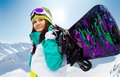 Snowboarder young woman with a snowboard on a background of mountains Stock Photo