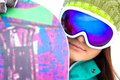 Snowboarder young woman in sport sunglasses with a snowboard close up Stock Photography