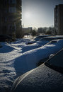 Snowbound cars in the parking lot snow covered parked under deep snow courtyard block of flats and clear blue sky with raised sun Stock Photography