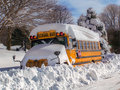 Snowbound school bus kids delight of another snow day covered by side road trapped by plowed neighborhood street Royalty Free Stock Photography