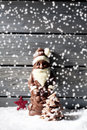Snowfall with santa claus star shaped christmas decoration chocolate christmas tree on heap of snow against wooden background Royalty Free Stock Photo