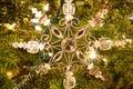 A snowflake Christmas ornament on a fur tree.