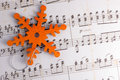 Snowflake christmas ornament orange wooden with a silver metallic cords on a background of sheet music Stock Photography