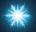 Snowflake sparkles in a shape of on the blue background Royalty Free Stock Image