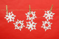 Snowflakes produced by child hanging on red background Stock Photography