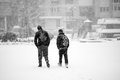 Snowing urban landscape with people