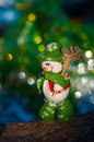 Snowman with a broom on a background of blurred Christmas tree Royalty Free Stock Photo