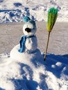 Snowman with broom in hat and scarf stands on ice rink Royalty Free Stock Photo