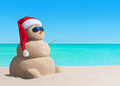 Snowman in Christmas Santa hat and sunglasses at sea beach Royalty Free Stock Photo