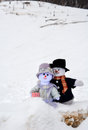 Snowman couple cuddle at snow hills a whimsical pair of people enjoy an outing in the with large behind them Royalty Free Stock Photography