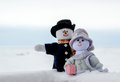Snowman couple pose in the snow a whimsical pair of people enjoy an outing Royalty Free Stock Photo