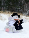 Snowman couple sight seeing a whimsical pair of snow people enjoy an outing in the snow Stock Photo