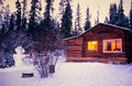 Snowman cozy illuminated log cabin winter vacation Royalty Free Stock Photo