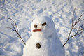 Snowman creature standing in winter landscape hand made by children fun and playing with snow Royalty Free Stock Image