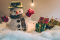 Snowman and light bulb stand among pile of snow at silent night, Merry christmas and Happy new year night. Royalty Free Stock Photo