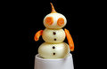Snowman made ​​from onions and carrots on black background Stock Image