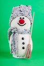 Snowman souvenir smiling on a green backgroung Royalty Free Stock Photos