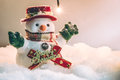 Snowman stand among pile of snow at silent night with a light bulb Royalty Free Stock Photo
