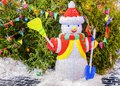 Snowman under tree with toy ornaments and lights Royalty Free Stock Photo