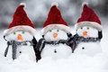 Snowmen with christmas hats wih and scarfs sat in the snow Stock Photos