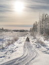 Snowmobile heading into sunlight a on a trail the distance and distant Stock Photography