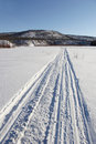 Snowmobile trail on frozen river the outgoing to the hills Royalty Free Stock Photos