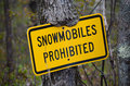 Snowmobiles prohibited sign on tree snowmobile nature trail partially overgrown by treebark Stock Photo