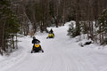 Snowmobiles riding on forest trail in the adirondacks two groomed through Royalty Free Stock Image