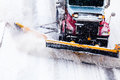 Snowplow removing the snow from the highway truck during a cold snowstorm winter day Stock Images
