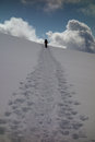 Snowshoeing uphill a lone person silhouetted along a trail up a snowy hillside Stock Image
