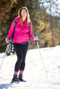 Snowshoes active smiling woman in the snow winter sports hiking at foot of a young on vacation sunglasses and ski clothing a Stock Photo
