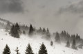 Snowstorm on high mountain slope with ropeway in background Stock Images