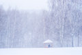 Snowstorm in the park an unrecognizable person finds a shelter under roof of small and open summerhouse christmas season Stock Images