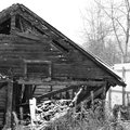 Snowy abandoned burned-out fire wooden black house. Royalty Free Stock Photo