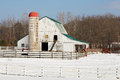 Snowy barnyard a white barn and silo capped with a red top stand next to a fenced in corral on a farm Stock Photography