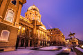 Snowy buda castle in budapest under a purplish blue sky main facade of the historic royal palace at nightfall hungary at night Stock Images