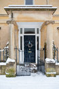 Snowy christmas entrance stone portico covered in snow leading to a traditional door with a wreath Stock Images