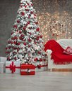 Snowy Christmas tree with red gifts before bokeh lights and wreath decoration on the wall with present boxes in the comfy room in Royalty Free Stock Photo